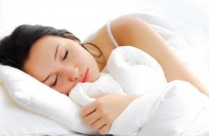 Beautiful woman lying and sleep on the snowy bed